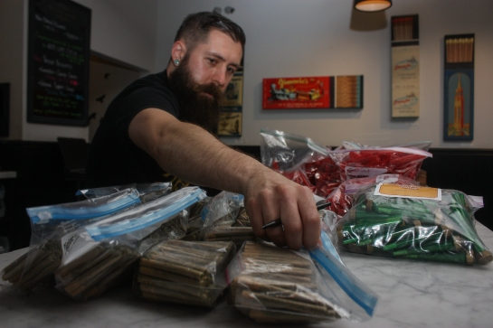 "General manager Chase Chambers reaches for a bag of 100 prerolled marijuana ""joints"" during inventory at The Apothecarium dispensory in San Francisco / Photo by Frank Ladra"