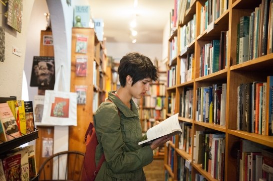 Student, Mission resident and frequent customer Haley Grey, 17, looks for a good read at Adobe Books & Arts Cooperative on a recent afternoon. (Photo by Ekevara Kitpowsong/ Bay News Rising)