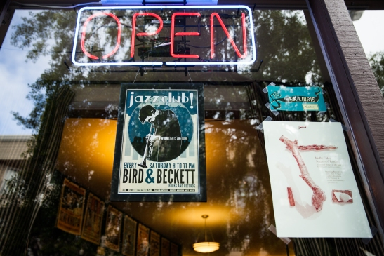 Posters promoting live jazz and an in-house gallery festoon the front window of Bird & Beckett Books and Records in Glen Park. (Photo by Ekevara Kitpowsong/ Bay News Rising)