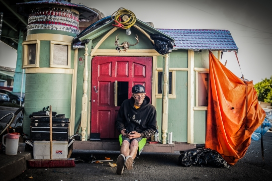 Brian Devlin relaxes on the front porch of his tiny home next to Highway 101 in San Francisco. (Photo by Ekevara Kitpowsong/ Bay News Rising)