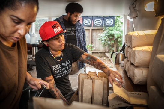(L-R) Warehouse-manager-in-training Celeste Freeman, part-time roaster Jess Llarinas, and operation manager, Antoine Hicks, work together at production space inside Red Bay Coffee's roasting lab in Oakland. (Photo by Ekevara Kitpowsong/ Bay News Rising)