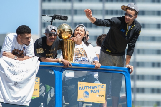 Warriors MVP Steph Curry waves to fans while teammate Andre Iguodala holds the championship trophy. (Photo by Khaled Sayed/Bay News Rising)