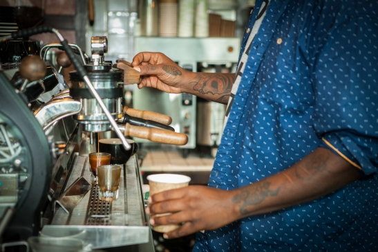 A part-time barista, Milan Hawthorne, 35, a.k.a. BeatsMe, makes a cappuccino for customer at the Chasing Lions Cafe located on Phelan Avenue, San Francisco on Wednesday, July 22, 2015. (Photo by Ekevara Kitpowsong/Bay News Rising)