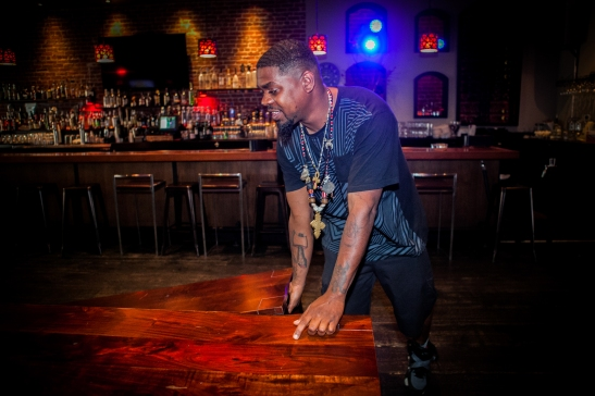 "A bar-back Milan Hawthorne ""BeatsMe"" sets up the tables and seats before the opening time at the Liege Spirits Lounge in Oakland on Friday afternoon, July 24, 2015. (Photo by Ekevara Kitpowsong/Bay News Rising)"