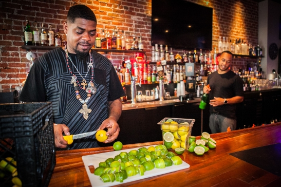 "(L-R) A bar-back Milan Hawthorne ""BeatsMe"" cuts a full basket of limes preparing for drinks while his colleague, the bartender Stephen Sloper makes a drink at the Liege Spirits Lounge in Oakland on Friday, July 24, 2015. (Photo by Ekevara Kitpowsong/Bay News Rising)"