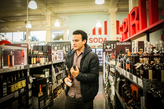 Homero Hidalgo, 35, works part time as postmates courier, buying liquors for customer who requested delivery order through the Postmates app, at BevMo! store on Van Ness Avenue, Friday, July 17, 2015. (Photo by Ekevara Kitpowsong/Bay News Rising)