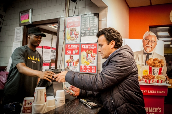 (L-R) A cashier Kelii Agee receives the food order from Homero Hidalgo, 35, part time postmates courier who placing order at KFC/Taco Bell on Duboce Avenue for the customer who requested delivery through the Postmates app on Friday, July 17, 2015. (Photo by Ekevara Kitpowsong/Bay News Rising)