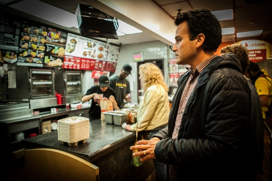 Homero Hidalgo, 35, part time postmates courier waits inside KFC/Taco Bell on Duboce Avenue to pick up the food order for the customer who requested delivery through the Postmates app on Friday, July 17, 2015. (Photo by Ekevara Kitpowsong/Bay News Rising)