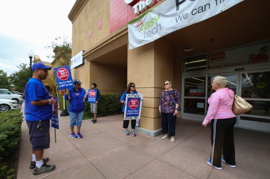 Postal workers Michael Rodriguez and Silvia Montes explain their concerns to passersby outside a Pleasant Hill Staples on Thursday, July 9. (Emilia Rosales/Bay News Rising)