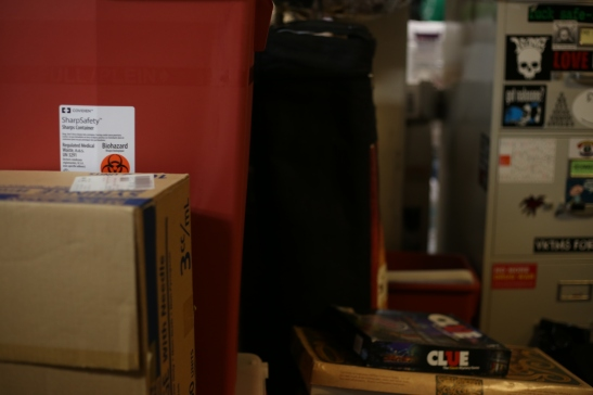 A sharps container is stored next to a stack of board games in the basement of Haight resident Kathleen Ryan on June 22, 2016. Ryan offered her home up to the Homeless Youth Alliance as a temporary office space after the non-profit has been unable to secure a new lease. Photo by Kelsey Lannin