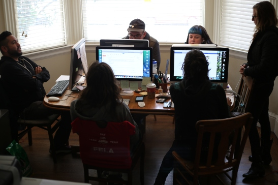 Six of the 10 Homeless Youth Alliance staff sit at the dining room table of a Haight resident, which serves as their temporary office space of two years, on June 22, 2016. Photo by Kelsey Lannin